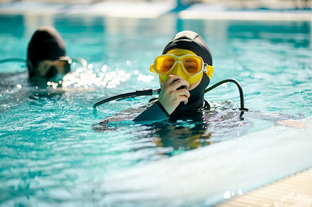 Female diver and male divemaster in scuba gear, dive lesson in diving school. teaching people to swim underwater, indoor swimming pool interior on background