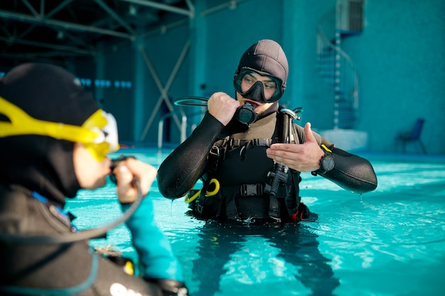 Female diver and male divemaster in scuba gear, lesson in diving school. teaching people to swim underwater, indoor swimming pool interior on background