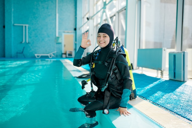 Female diver in scuba suit sitting at the poolside, diving school. teaching people to swim underwater, indoor swimming pool interior on background
