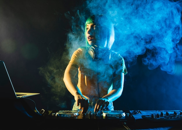 Female dj in club covered by colorful smoke