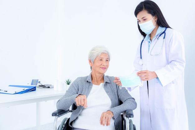 女性医師は、保護フェイスマスクの着用について高齢患者にアドバイスします。コロナウイルスパンデミック。 covid19アウトブレイク。