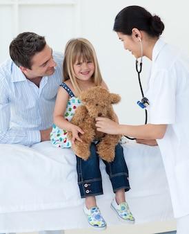 女性の医者と幸せな女の子テディベアを調べる
