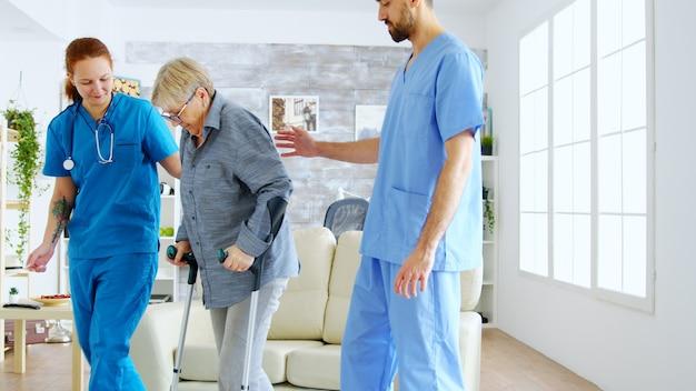 松葉杖を持った老婆がソファから立ち上がって散歩するのを手伝う女医師と助手