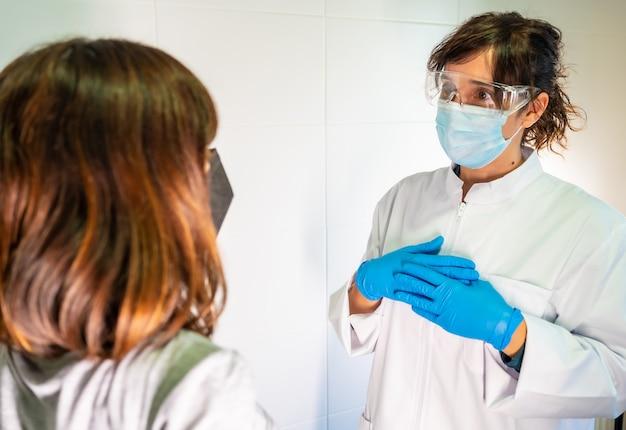 定期的な相談で女性医師とフェイスマスクの患者。抗体は、人口を免疫します。