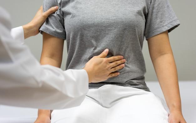 Женщина-врач осматривает при пальпации живота пациентки, сидящей на кровати в клинике.