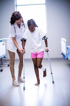 Женщина-врач помогает девочке ходить с костылями в палате