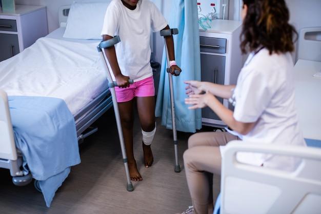 女性医師が病棟で松葉杖で歩く女の子を支援