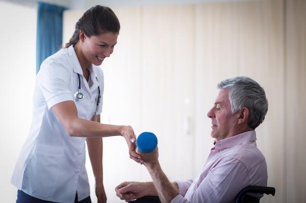 Женский доктор помогая старшему человеку в поднимаясь гантели