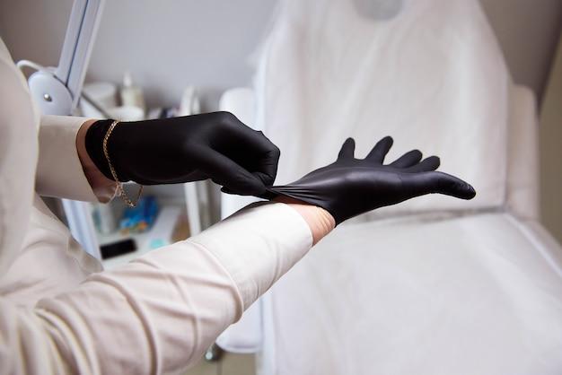 女性医師の美容師は滅菌手袋を着用し、クライアントを受け入れる準備をします。