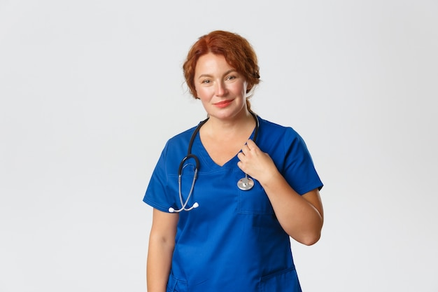 Female doctor in blue scrubs with stethoscope smiling at camera, treating patients in hospital standing on grey