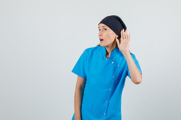 Female doctor in blue uniform, black hat holding hand behind ear to listen and looking focused