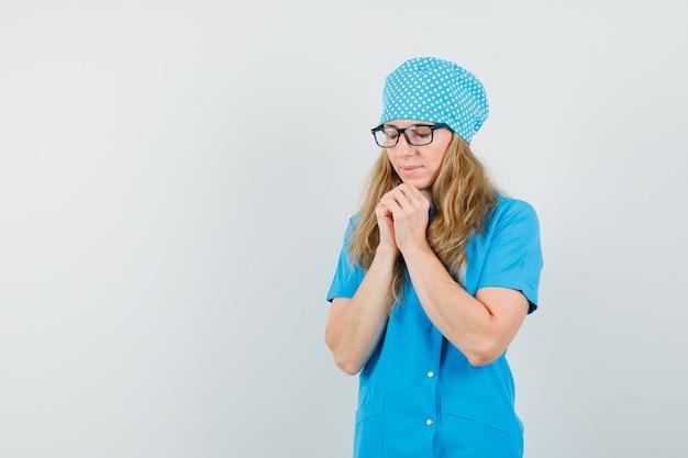 Dottoressa in uniforme blu stringendo le mani nel gesto di preghiera e guardando speranzoso