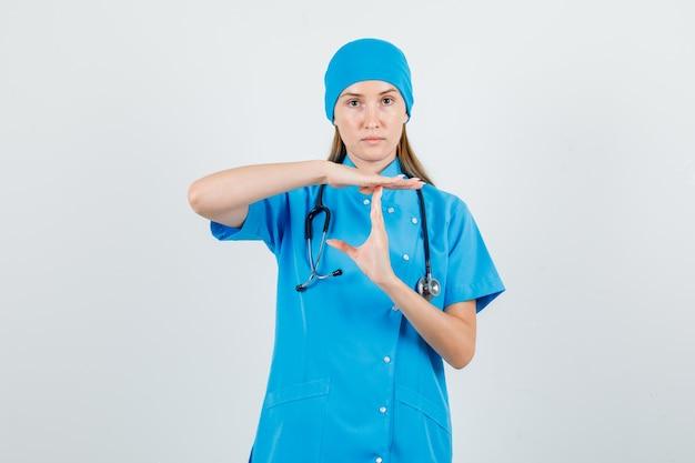 Medico femminile in uniforme blu che fa gesto di pausa di tempo e che sembra rigoroso