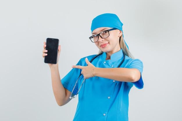 Dottoressa in uniforme blu, occhiali che punta il dito sullo smartphone e sembra allegro