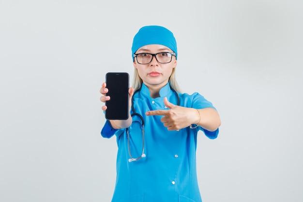 Dottoressa in uniforme blu, occhiali puntare il dito sullo smartphone