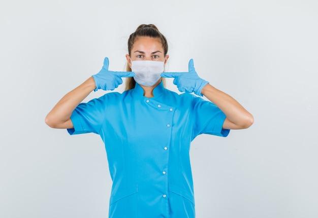 Dottoressa in uniforme blu, guanti che punta alla sua maschera e guardando attento