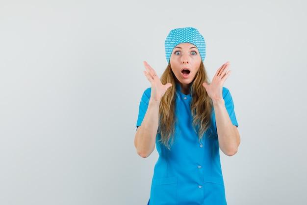 Dottoressa in uniforme blu tenendosi per mano vicino alla bocca e guardando ansioso