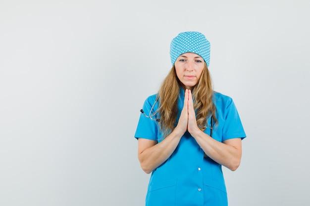 Dottoressa in uniforme blu tenendosi per mano nel gesto di preghiera e guardando speranzoso