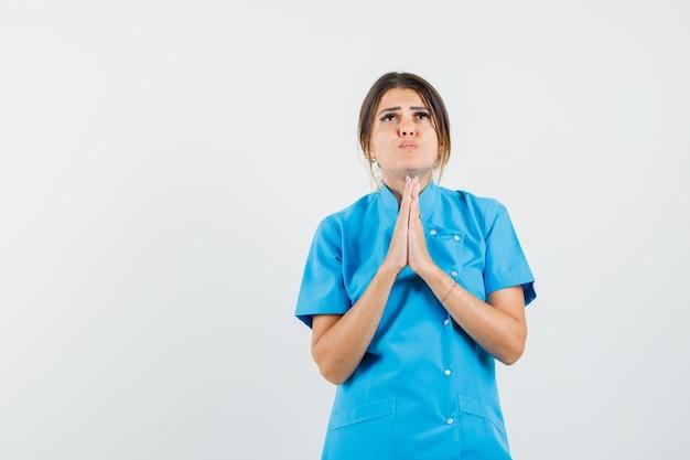 Dottoressa in uniforme blu che si tiene per mano in un gesto di preghiera e sembra speranzosa