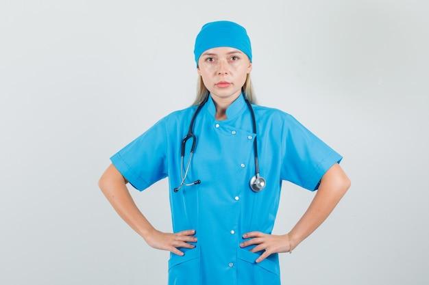 Dottoressa in uniforme blu che tiene le mani sulla vita e che sembra seria