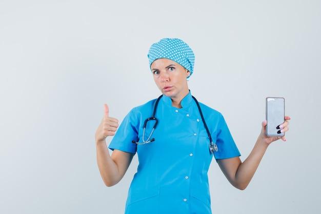 Dottoressa in uniforme blu che tiene il telefono cellulare, mostrando il pollice in alto, vista frontale.