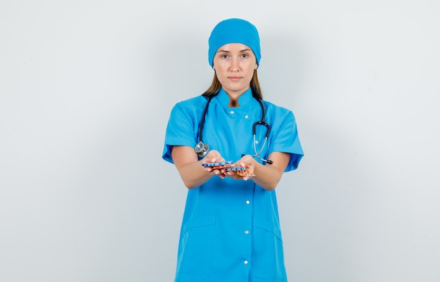 Medico femminile in uniforme blu che tiene confezioni di pillole e che sembra serio