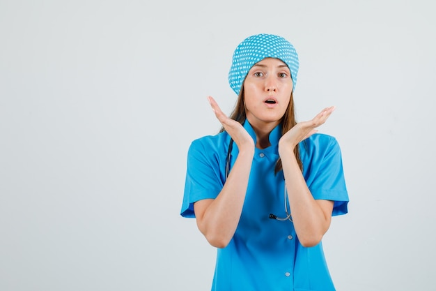 Medico femminile in uniforme blu che tiene le palme sollevate e che sembra sorpreso