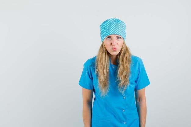 Dottoressa in uniforme blu mantenendo le labbra piegate e guardando divertente
