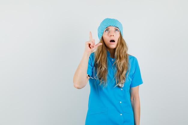 Medico femminile in uniforme blu che osserva in su con il dito in su e che sembra sorpreso