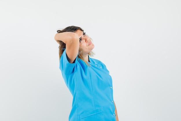 Dottoressa in uniforme blu che guarda in alto con la mano sui capelli e sembra elegante