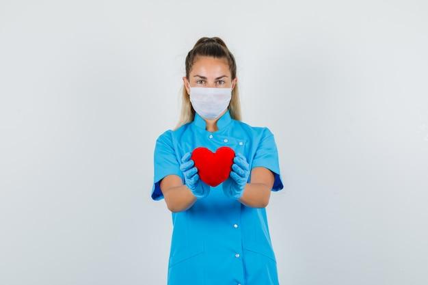 Dottoressa in uniforme blu, maschera, guanti che tengono cuore rosso