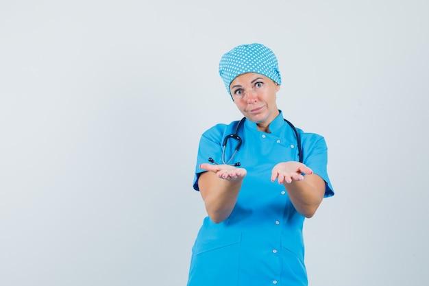 Dottoressa in uniforme blu che offre qualcosa e che sembra dolce, vista frontale.