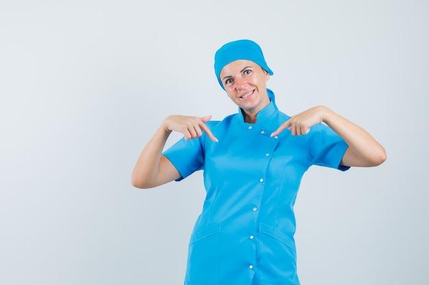Dottoressa in uniforme blu che punta a se stessa e guardando fiducioso, vista frontale.