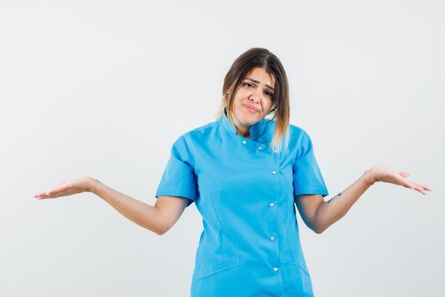 Dottoressa in uniforme blu che mostra un gesto impotente e sembra triste