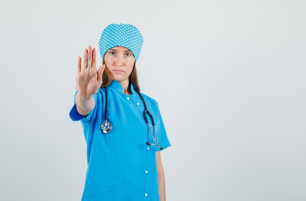 Female doctor in blue uniform showing stop gesture and looking serious, front view.