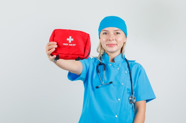 Female doctor in blue uniform showing up first aid kit and looking cheerful
