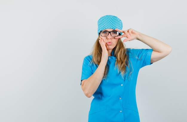 Female doctor in blue uniform showing v-sign near eye and pouting lips