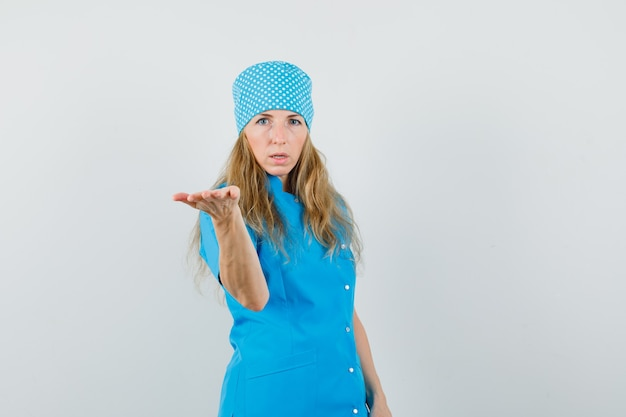 Female doctor in blue uniform stretching hand in puzzled gesture