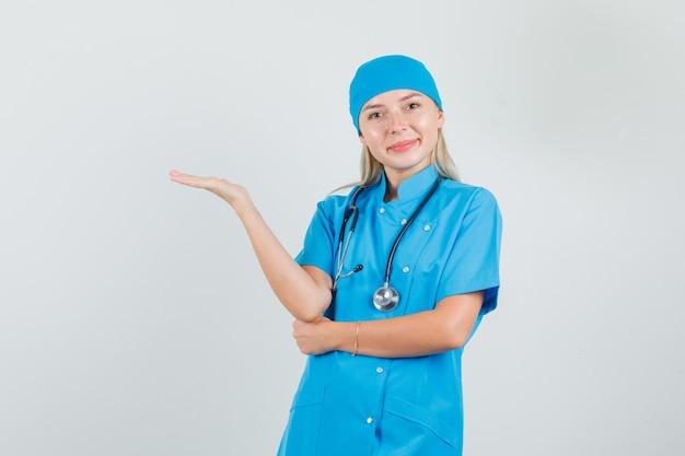 Dottoressa in uniforme blu che dà il benvenuto o mostra qualcosa e sembra allegra