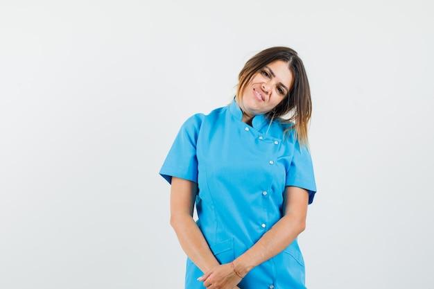 파란색 유니폼을 입고 어깨에 머리를 숙이고 낙관적 인 여성 의사