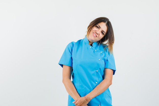 Female doctor bowing head on shoulder in blue uniform and looking optimistic
