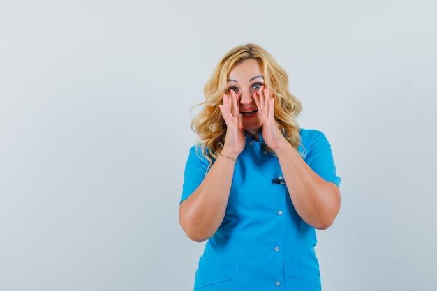 파란색 제복을 입은 시끄러운 목소리로 누군가를 부르고 텍스트에 대한 희망적인 공간을 찾는 여성 의사