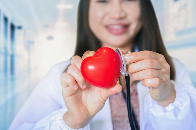 심장 모델, 의료 건강 관리 및 의사 직원 서비스 개념을 들고 있는 여성 의사 심장 전문의