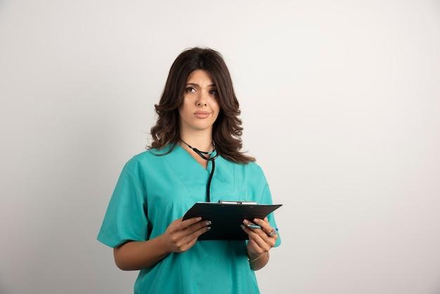 クリップボードに重要な文書を運ぶ女性医師。