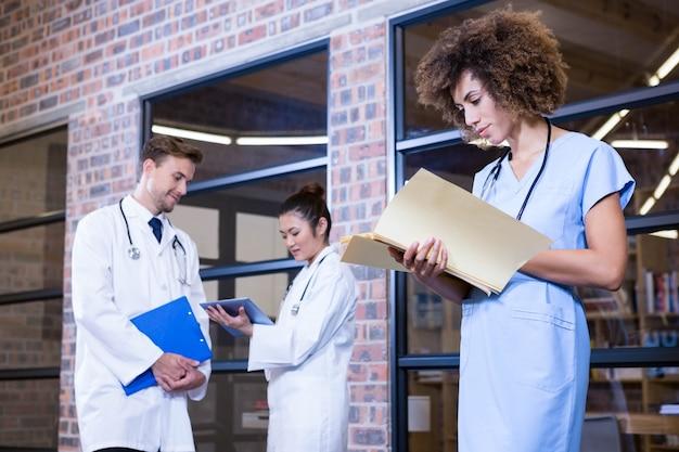 라이브러리와 동료 뒤에 서 파일을 확인하고 논의하는 여성 의사
