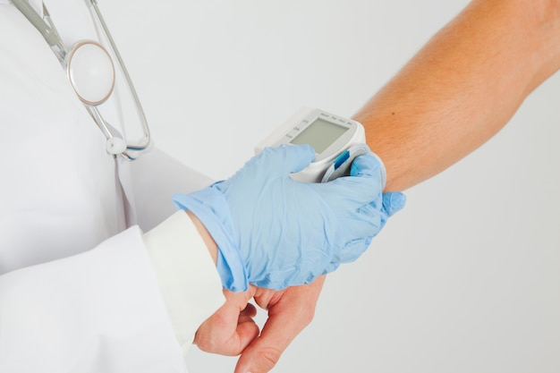 Female doctor checking blood pressure at arm