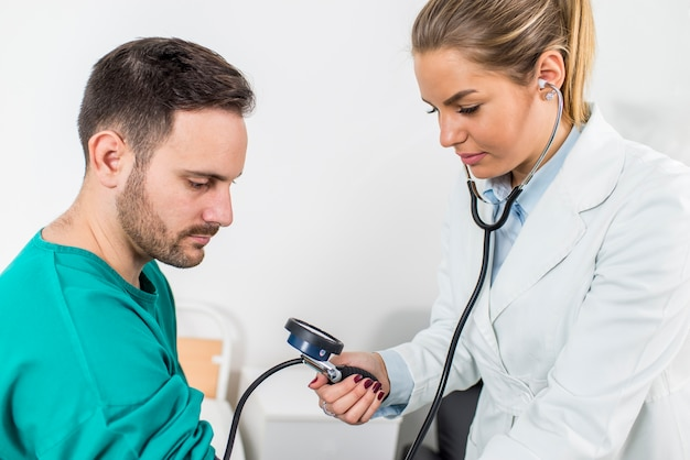 Female doctor checking blood pressure of a patient at clinic