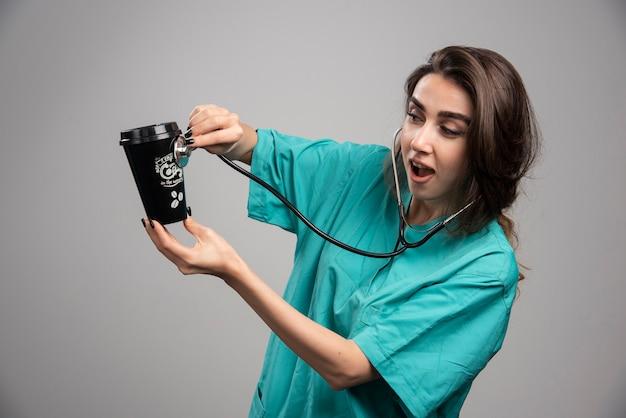 Medico femminile che controlla la tazza di caffè con lo stetoscopio. foto di alta qualità