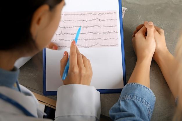 Женщина-врач, проверка результатов электрокардиограммы с пациентом