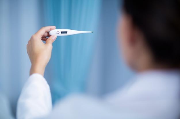 女医がデジタル温度計からの発熱をチェック